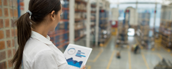Woman with clipboard in warehouse working in Supply Chain and Logistics.